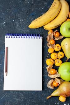 Vista de cima, par de frutas vermelhas, bananas amarelas com maçãs verdes frescas, peras e cerejas doces, bloco de notas na mesa escura frutas bagas frescas vitaminas saudáveis