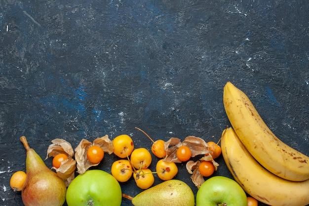 Vista de cima, par de frutas vermelhas, bananas amarelas com maçãs verdes frescas, peras e cerejas doces no fundo azul escuro vitamina de frutas frescas de frutas vermelhas