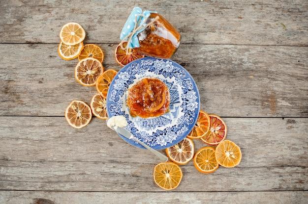Vista de cima para a deliciosa geléia de laranja no pão servido no prato azul ornamentado perto da jarra de vidro e laranjas secas na mesa de madeira