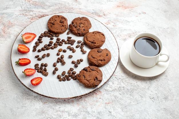 Vista de cima para baixo biscoitos de chocolate deliciosos com gotas de chocolate e morangos na superfície branca biscoito açúcar doce assar biscoitos