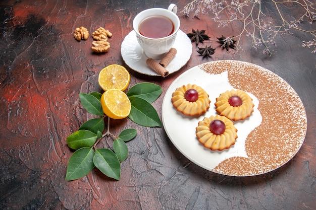 Vista de cima para baixo, bolinhos com uma xícara de chá na mesa escura, bolo de biscoito com açúcar