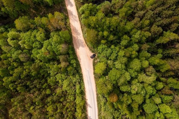 Vista de cima para baixo da estrada rural com o carro na floresta no verão, drone disparado