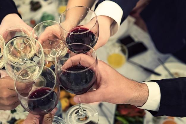Vista de cima para baixo das mãos masculinas e femininas com copos cheios de vinho acima da mesa do restaurante. brindes e copos tilintando em um jantar. beber vinho em um banquete. festeje um evento.
