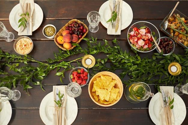 Vista de cima para baixo de pratos coloridos de verão em uma mesa de jantar de madeira decorada com folhas frescas e elementos florais durante a festa ao ar livre