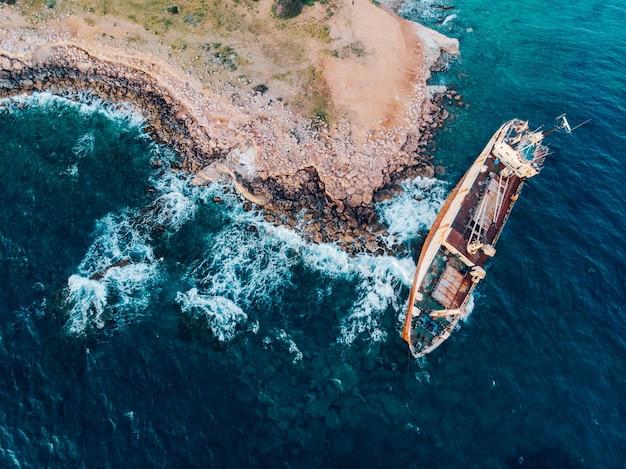Vista de cima para baixo de um navio encalhado perto da costa, tiro do drone.