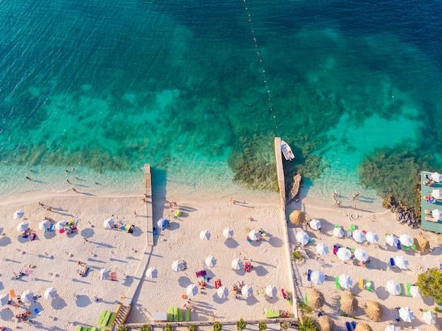 Vista de cima para baixo de uma bela praia de areia branca com águas azul-turquesa e pessoas relaxantes em um dia ensolarado. ksamil, albânia.