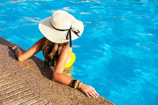 Vista de cima para baixo de uma jovem com chapéu de palha amarelo, descansando na piscina com águas azuis claras em um dia ensolarado de verão.