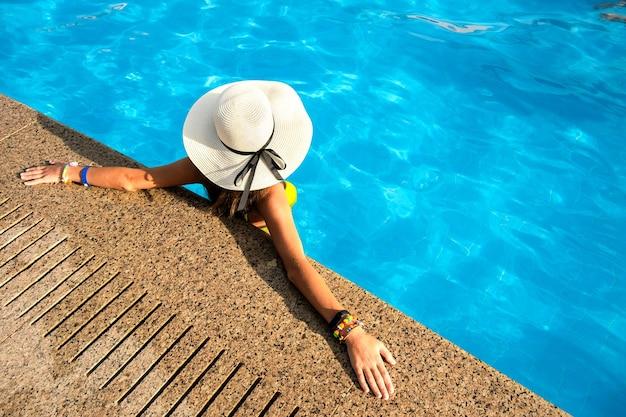 Vista de cima para baixo de uma jovem com chapéu de palha amarelo, descansando na piscina.