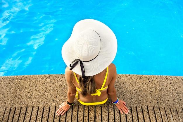 Vista de cima para baixo de uma jovem com chapéu de palha amarelo, descansando perto da piscina com águas azuis claras em um dia ensolarado de verão.