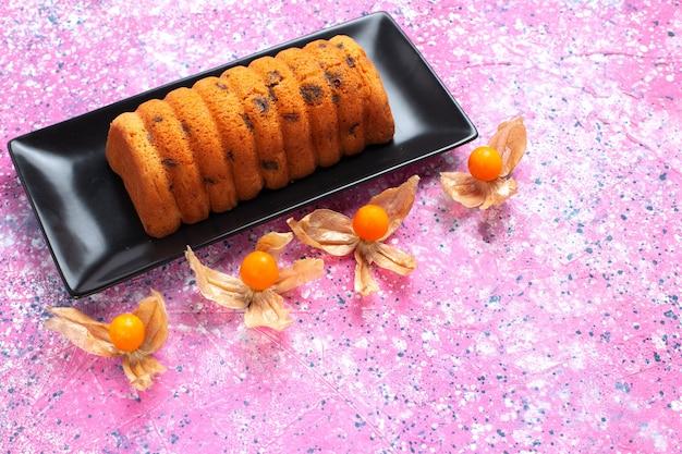 Vista de cima para baixo, delicioso bolo assado dentro de uma fôrma preta com fisálises na mesa rosa.