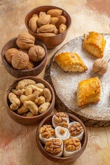 Vista de cima para baixo deliciosos bolos doces com nozes diferentes em uma mesa de madeira, torta de biscoito