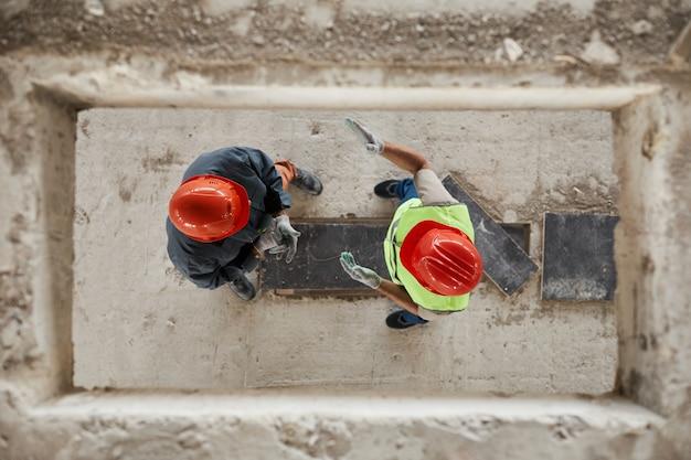 Vista de cima para baixo em dois trabalhadores da construção civil usando capacetes no espaço da cópia do local da costrução