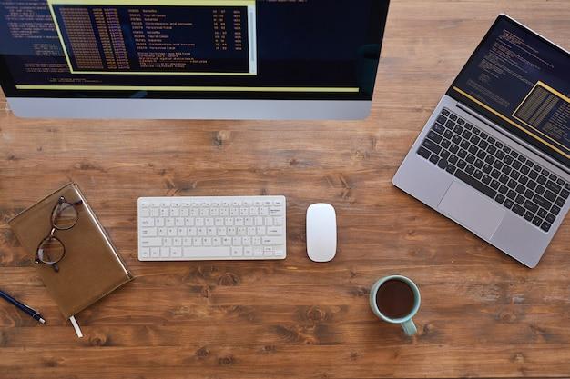 Vista de cima para baixo em um local de trabalho contemporâneo com dois computadores e uma xícara de café na mesa de madeira texturizada, copie o espaço
