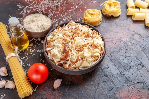 Vista de cima para baixo fatiado de massa cozida com arroz em superfície escura massa prato massa escura