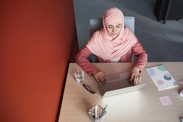 Vista de cima para baixo na jovem empresária usando lenço na cabeça, usando o laptop na mesa enquanto trabalha no escritório, copie o espaço