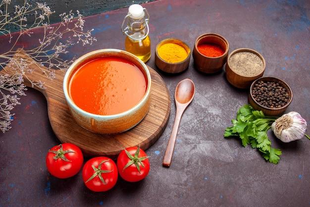 Vista de cima para baixo, saborosa sopa de tomate com tomates frescos e temperos no espaço escuro