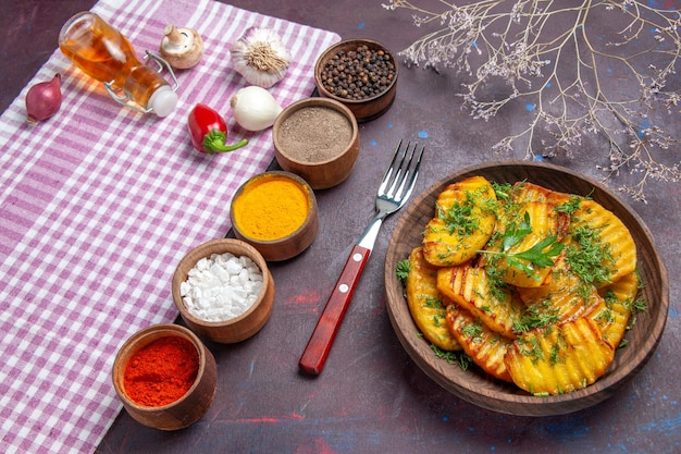 Vista de cima para baixo saborosas batatas cozidas prato delicioso com verduras e temperos na superfície escura jantar cozinhando prato de batata