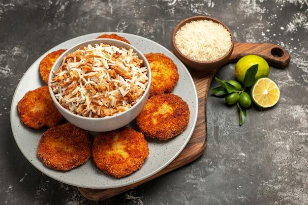 Vista de cima para baixo, saborosas costeletas fritas com arroz cozido em um prato de rissole de carne com superfície escura
