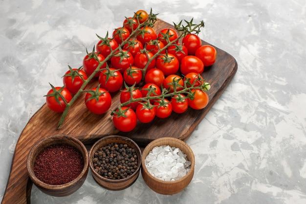 Vista de cima para baixo, tomates cereja frescos e vegetais inteiros maduros com temperos na mesa branca
