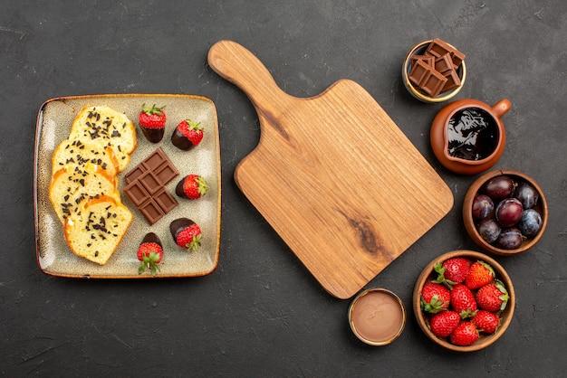 Vista de cima para bolo e morangos em uma tábua de madeira entre pedaços de bolo com chocolate à esquerda e tigelas com morangos e frutas vermelhas e calda de chocolate no lado direito da mesa