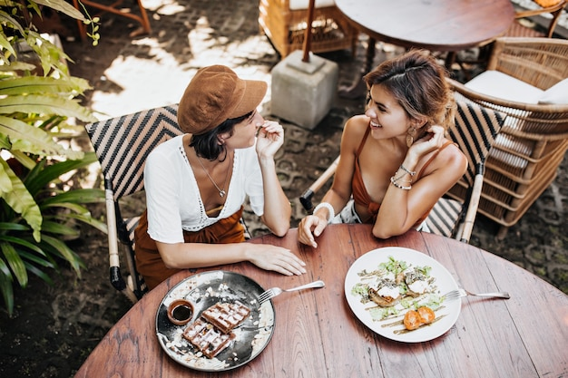 Vista de cima para mulheres bronzeadas em trajes elegantes conversando e saboreando comida saborosa em um café de rua