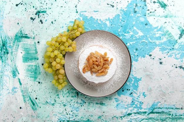 Vista de cima passas secas de uva com uvas verdes frescas na superfície azul-clara