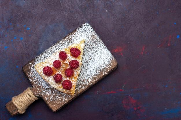 Vista de cima, pedaço de bolo assado com framboesas na mesa escura
