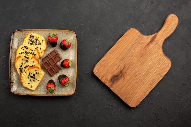 Vista de cima pedaços de bolo pedaços de bolo com chocolate e morangos e placa de cozinha marrom na mesa escura