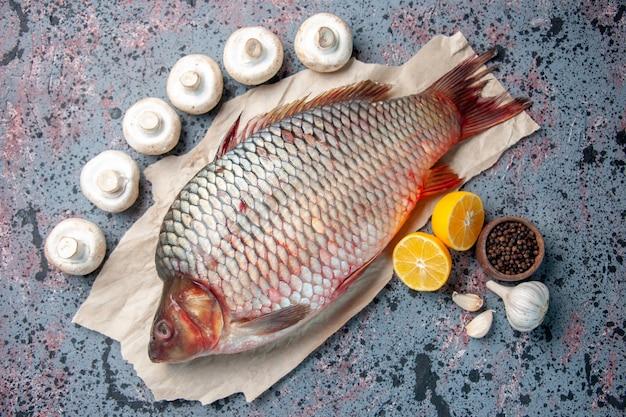 Vista de cima peixe cru fresco com cogumelos no fundo azul