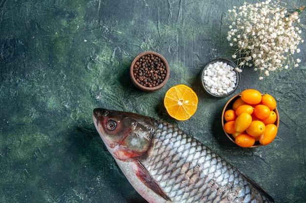 Vista de cima peixe cru fresco com kumquats em fundo escuro