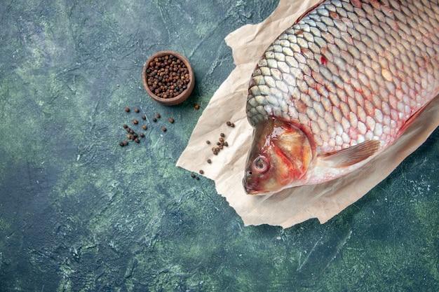 Vista de cima peixe cru fresco com pimenta em fundo azul escuro