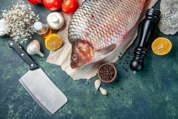 Vista de cima peixe cru fresco com tomate e cogumelos em fundo azul escuro