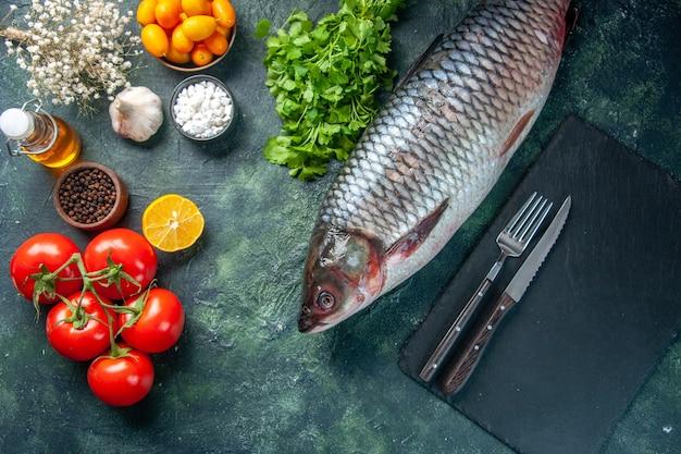 Vista de cima peixe cru fresco com tomate e verduras em fundo escuro