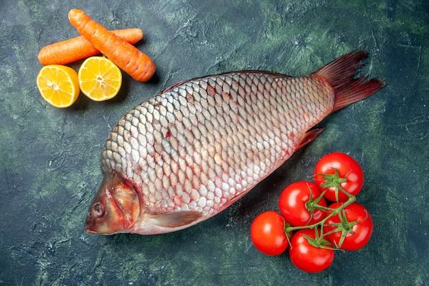 Vista de cima peixe cru fresco com tomate em fundo azul escuro
