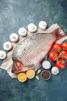 Vista de cima peixe cru fresco com tomate vermelho e cogumelos em fundo azul escuro