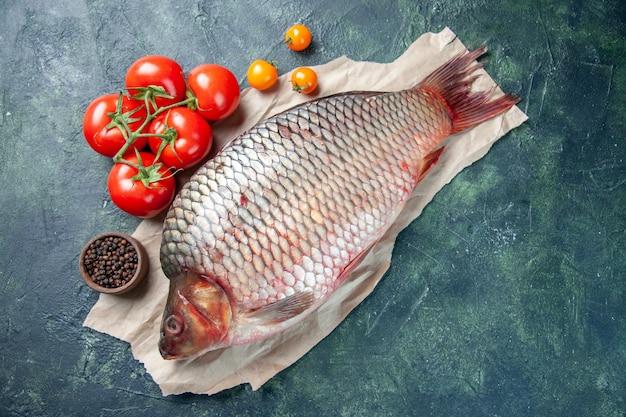 Vista de cima peixe cru fresco com tomate vermelho sobre fundo azul escuro