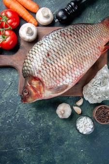Vista de cima peixe cru fresco na tábua com fundo azul escuro de tomates