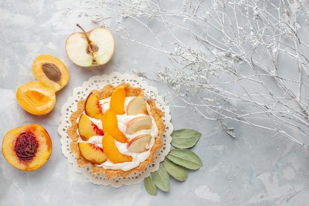 Vista de cima pequeno bolo cremoso com frutas fatiadas e creme branco junto com damascos frescos e pêssegos na mesa de luz branca bolo de frutas biscoito biscoito assar