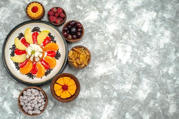 Vista de cima pequeno bolo cremoso com frutas fatiadas e passas na superfície branca torta de frutas bolo doce biscoito de açúcar