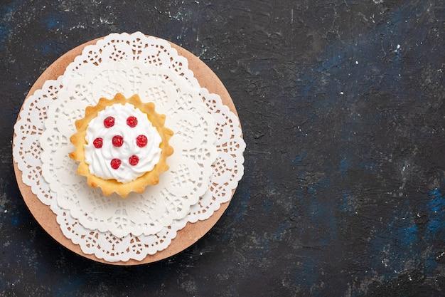 Vista de cima pequeno bolo cremoso com frutas vermelhas na superfície escura doce