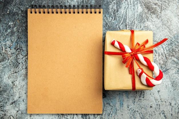 Vista de cima pequeno presente amarrado com fita vermelha caderno de doces de natal em fundo cinza