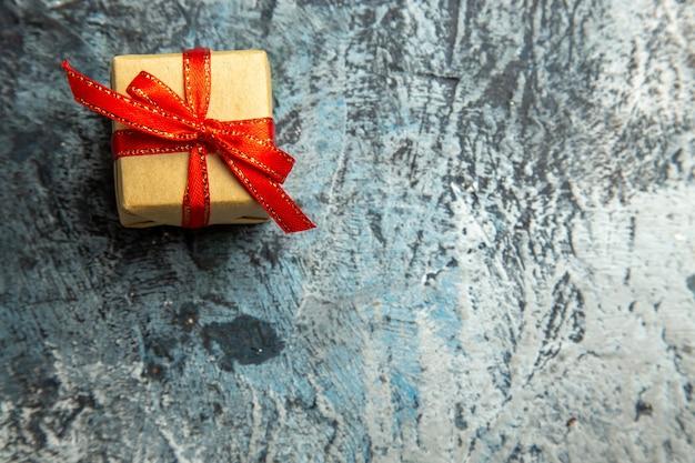 Vista de cima pequeno presente amarrado com fita vermelha em fundo escuro