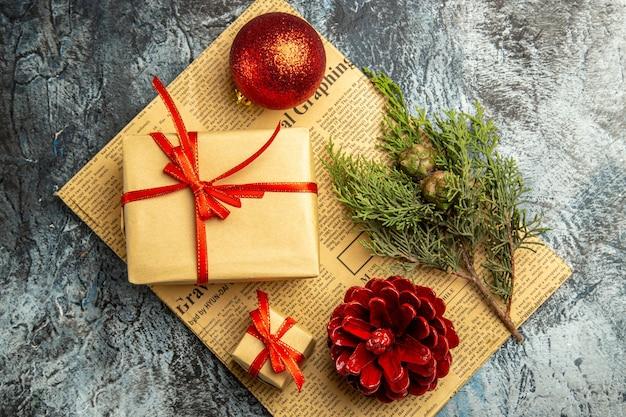 Vista de cima pequeno presente amarrado com fita vermelha ramo de pinheiro bola vermelha em jornal em superfície escura