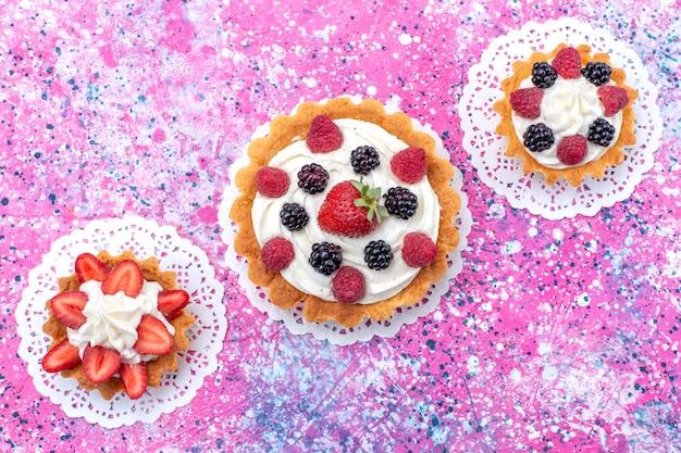 Vista de cima pequenos bolos cremosos com diferentes frutas silvestres na mesa branca clara.