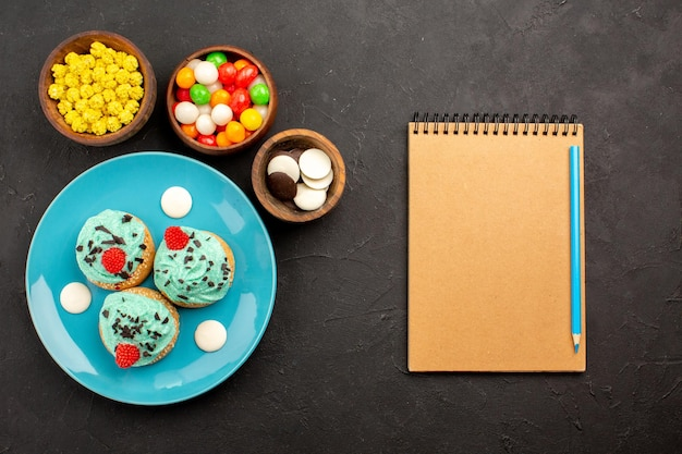 Vista de cima pequenos bolos cremosos com doces na mesa escura, sobremesa, bolo, biscoito, cor doce, creme