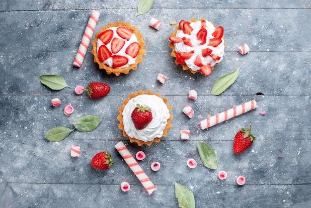 Vista de cima pequenos bolos cremosos com morangos fatiados e frescos junto com balas na superfície cinza bolo de frutas cor doce baga