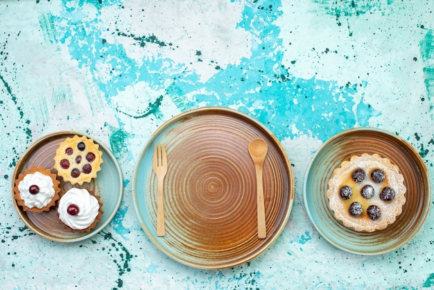 Vista de cima pequenos bolos deliciosos com creme e frutas no fundo azul claro bolo doce creme asse frutas
