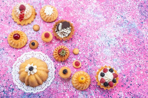 Vista de cima pequenos bolos deliciosos com creme junto com diferentes frutas no fundo brilhante bolo biscoito baga doce assar