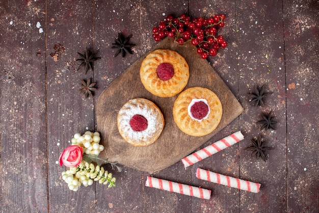 Vista de cima pequenos bolos deliciosos com framboesas e cranberries frescas, juntamente com balas na mesa de madeira marrom.