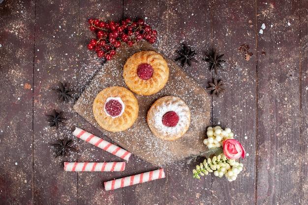 Vista de cima pequenos bolos deliciosos com framboesas e cranberries frescas junto com balas na mesa de madeira bolo doce açúcar frutas